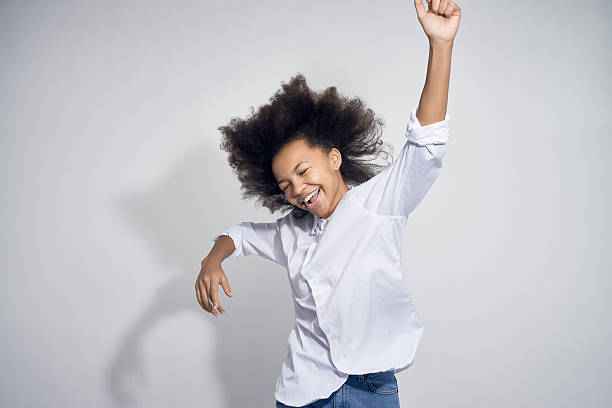 happy teenage girl dancing - african youth jumping for joy stock photos and pictures
