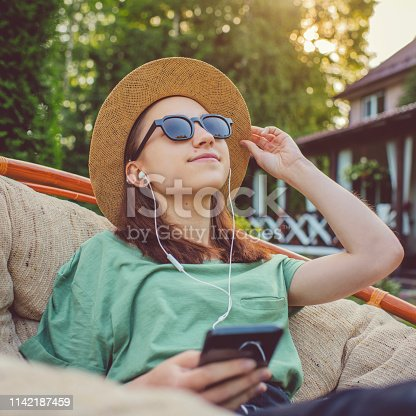 Cute teenager listening to music outdoors in summer