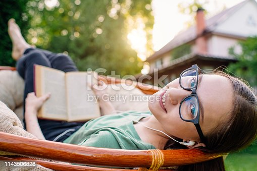 Cute girl with headset and smartphone enjoying summer evening