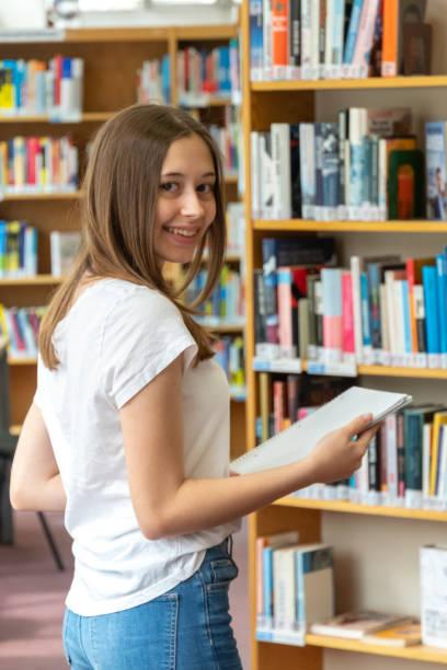 glückliches teenager-mädchen posiert in der schulbibliothek - deutsche bibliothek stock-fotos und bilder
