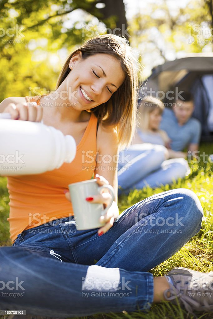 Happy teenage girl pouring coffee outdoors. royalty-free stock photo