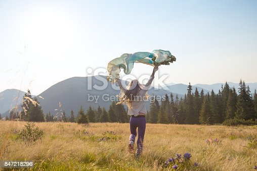 Happy teenage girl runs along the alpine meadow with a waving scarf in her hands. Amazing travel in a wilderness. Back view, back light