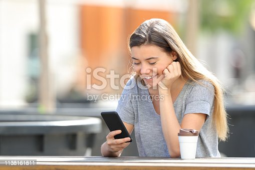 istock Happy teenage girl using a smart phone sitting in a park 1138161811