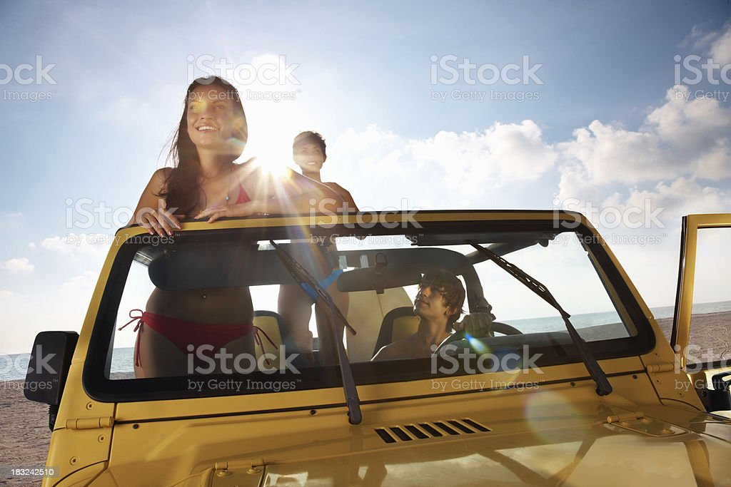 Happy teenage girl with her friends in jeep at beach royalty-free stock photo