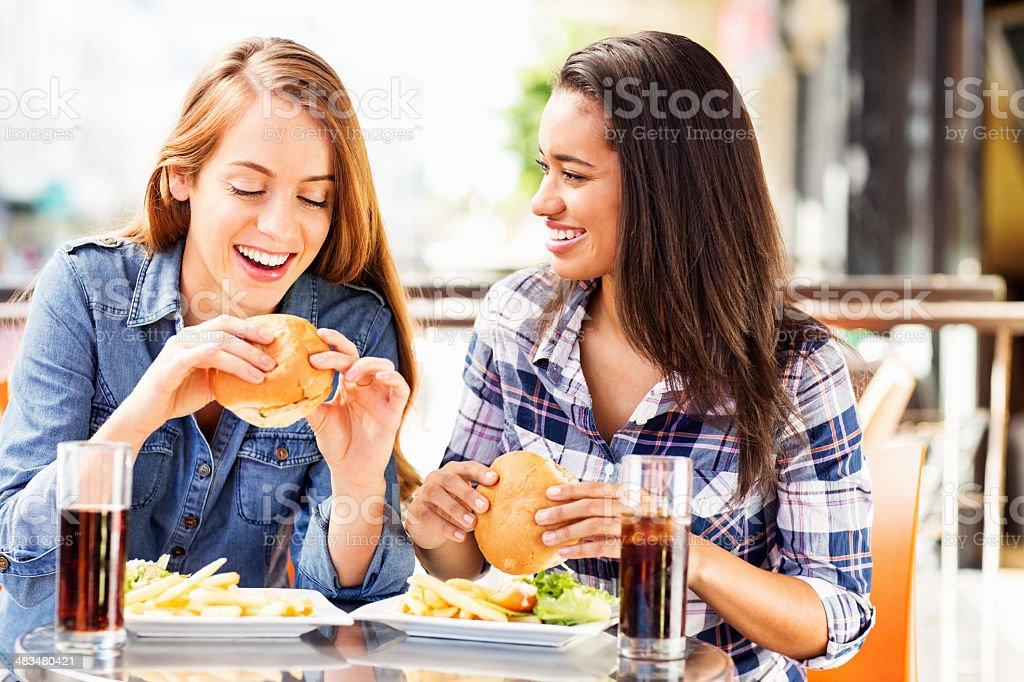 Happy teenage girls eating hamburgers royalty-free stock photo
