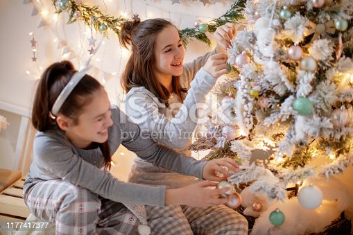 Two teenage girls in pajamas decorating the Christmas tree and having fun