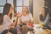 Happy teenage girls talking and laughing in a cafe.