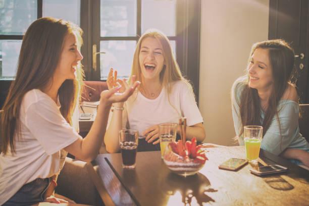 幸せな 10 代の少女の話とカフェで笑っています。 ストックフォト