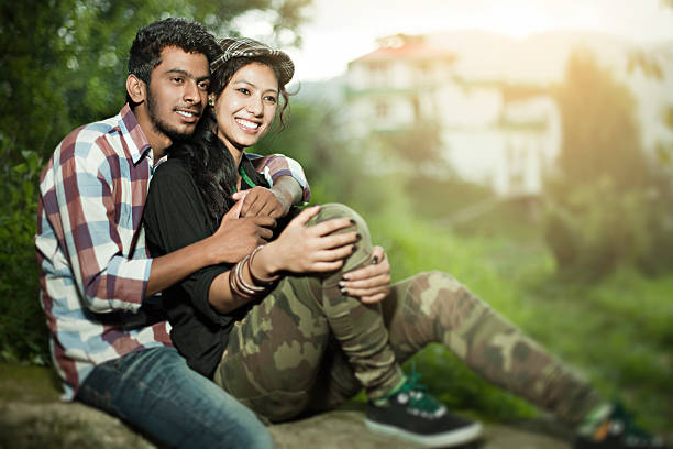Happy teenage lovers of different ethnicity together in tranquil place. Outdoor image of a happy teenage Asian boy embracing his girlfriend of different ethnicity in a tranquil place. The young lover couples are sitting on a wall in a green peaceful area. The boy is in full sleeve checkered shirt, jeans and the girl is in a full sleeve black shirt, military print pants, canvas shoes and a cap. Horizontal image with copy space and selective focus. romance stock pictures, royalty-free photos & images