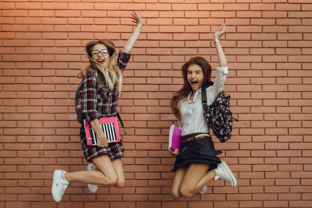 Happy teenage schoolgirls holding books and jumping stock photo