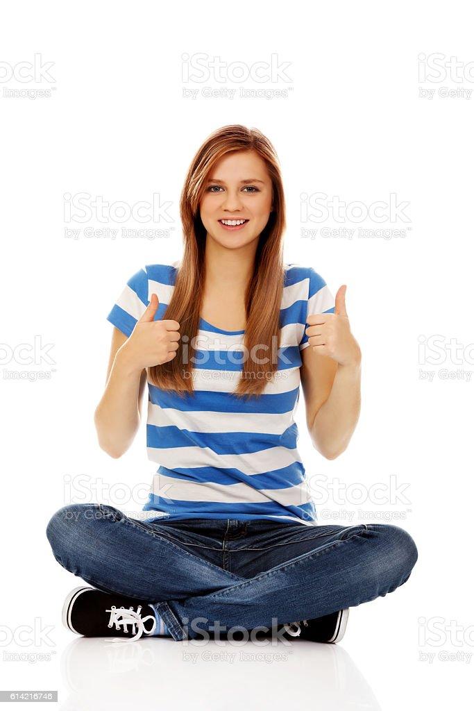 Happy teenage woman sitting with cross legged - Photo