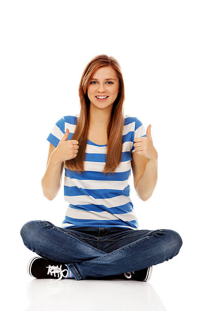 Happy teenage woman sitting with cross legged Happy teenage woman sitting with cross legged and showing OK sign cross legged stock pictures, royalty-free photos & images