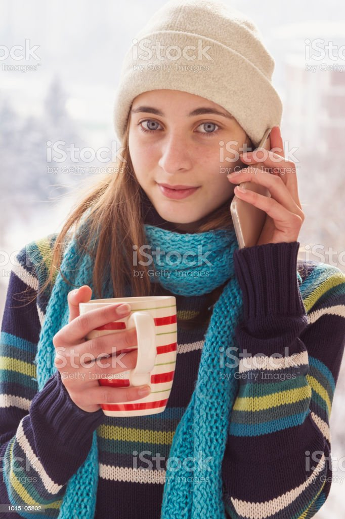 Happy young Caucasian teenage woman talking on the phone laughing...
