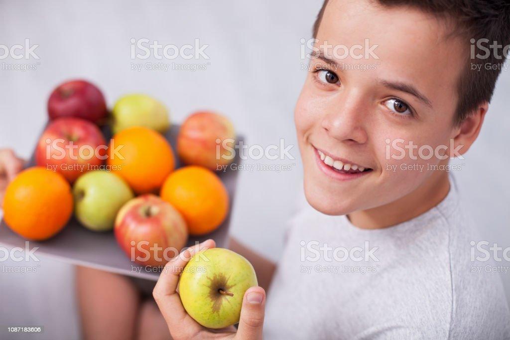 Glücklich Teenager Boy halten Sie einen Teller mit frischem Obst - Kommissionierung einen Apfel – Foto