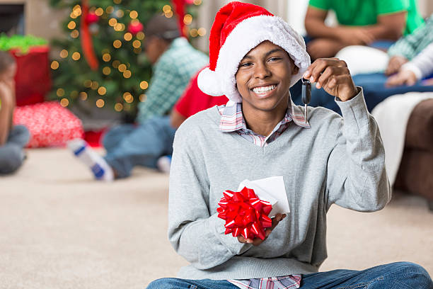 happy teenager gets keys to a car for christmas - autoschleifen stock-fotos und bilder
