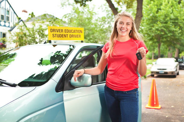 Happy Teenager Holding Car Key After Driver's License Exam A young Caucasian teenager girl standing next to her car holding her car key after the driver's license exam. She is happy and excited after passing the test. driving instructor stock pictures, royalty-free photos & images