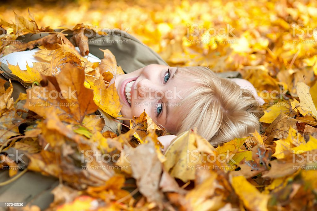 happy teenager in autumn leaves royalty-free stock photo