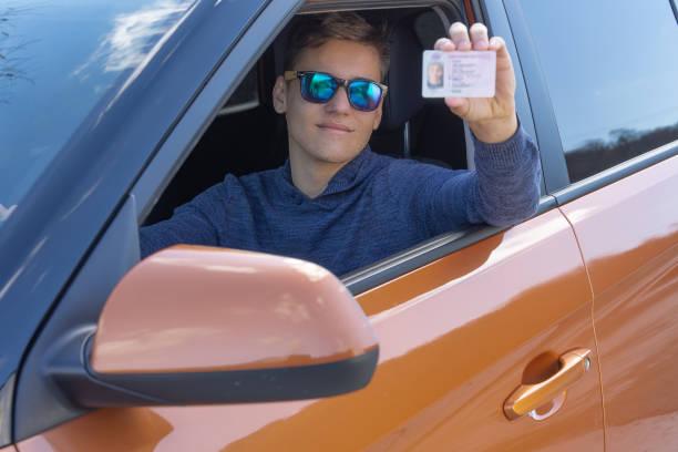 glücklicher teenager zeigt führerschein aus offenem autofenster fahrschulkonzept - führerschein stock-fotos und bilder
