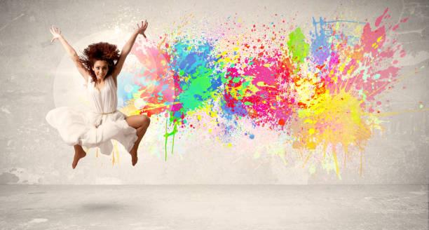 glücklich teenager springen mit bunten tinte splatter auf städtischen hintergrund - spaß sprüche stock-fotos und bilder