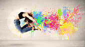 istock Happy teenager jumping with colorful ink splatter on urban background 883185518