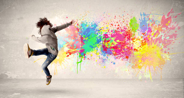happy teenager jumping with colorful ink splatter on urban background - tipo di danza foto e immagini stock