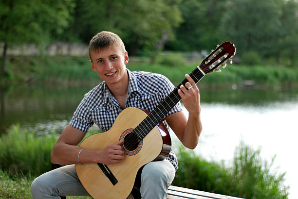 happy teenager playing guitar by the river stock photo