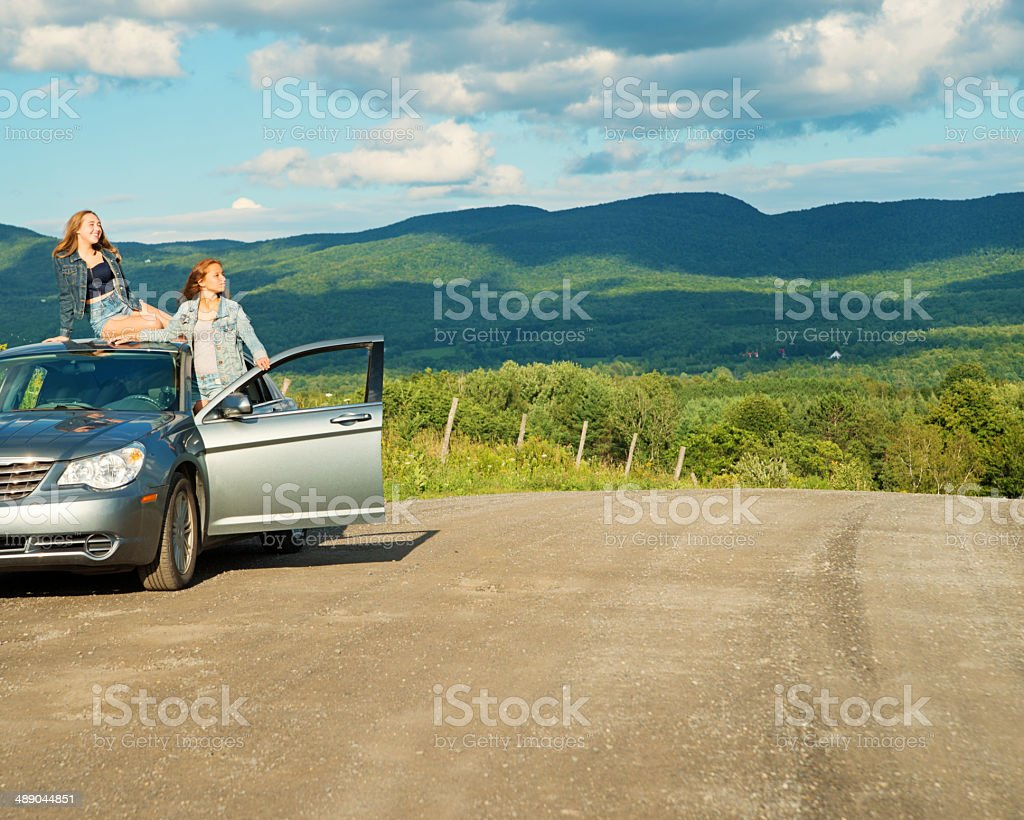 Happy teenagers on first road trip with parent's car. stock photo