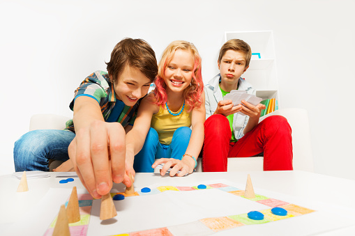 istock Happy teenagers play table game together at home 537701361