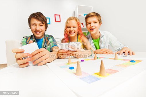 istock Happy teenagers playing table game holding cards 537701453