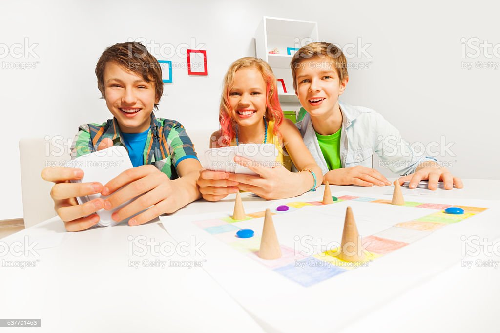 Happy teenagers playing table game holding cards stock photo
