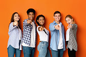 istock Happy teenagers pointing fingers at camera and smiling 1179954847