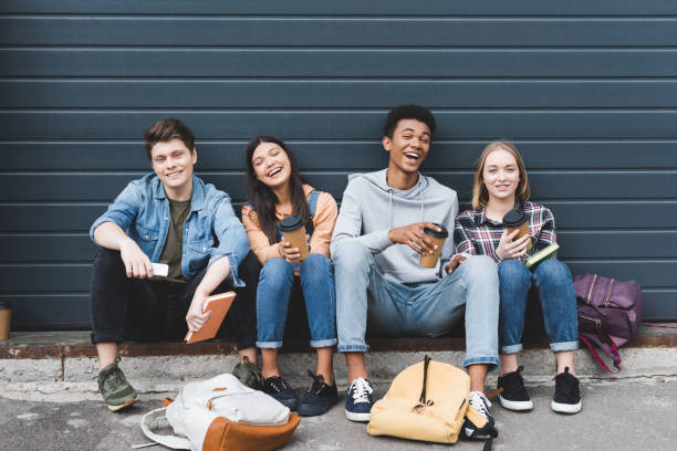 happy teenagers sitting, smiling, holding paper cups and looking at camera happy teenagers sitting, smiling, holding paper cups and looking at camera teenagers only stock pictures, royalty-free photos & images