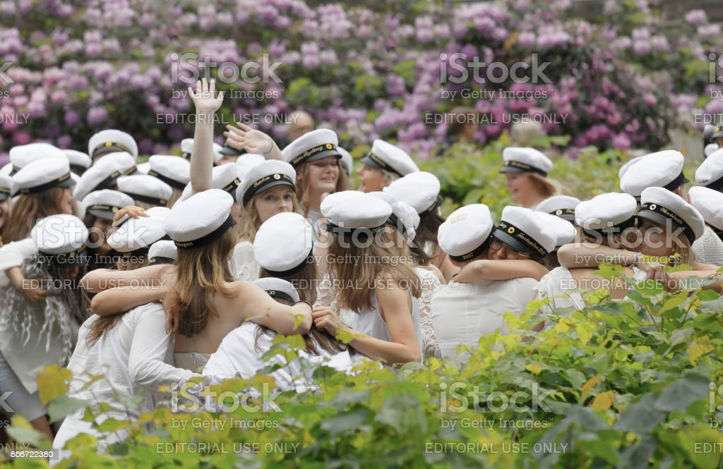 Happy teenagers wearing graduation caps hugging each other after graduation stock photo