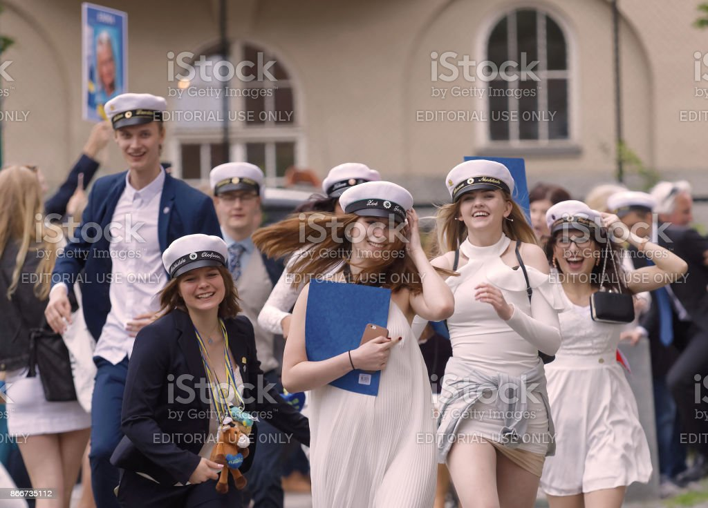 Happy teenagers wearing graduation caps running out from school after graduation stock photo