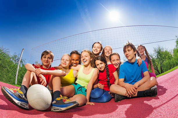 Happy teenagers who sit on volleyball game court stock photo