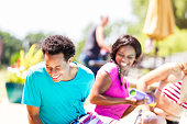 istock Happy teens laughing and playing together by the pool 584890278
