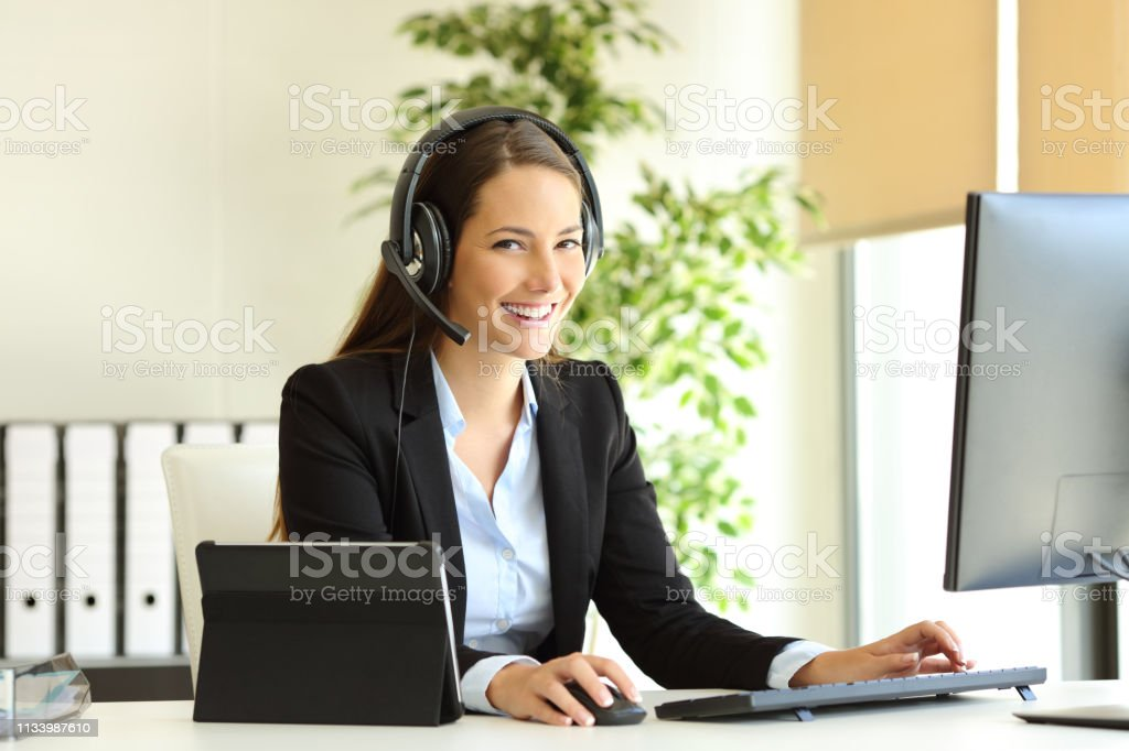 Happy tele marketer working looking at camera at office - Royalty-free A usar um telefone Foto de stock