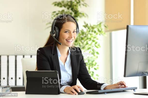 Happy Tele Marketer Working Looking At Camera At Office - Fotografias de stock e mais imagens de A usar um telefone