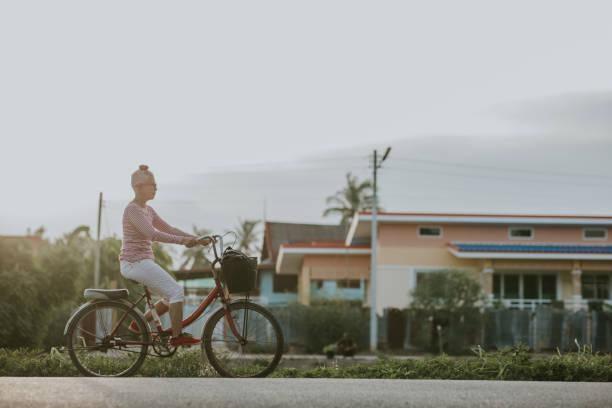 バスケットと自転車に乗って幸せなタイのシニア女性 - ストック写真 - showus ストックフォトと画像