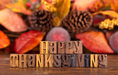 Happy Thanksgiving message written in wooden block letters with autumn background theme