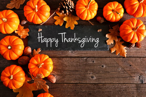 Happy Thanksgiving chalkboard sign with corner border of pumpkins and leaves over rustic wood stock photo