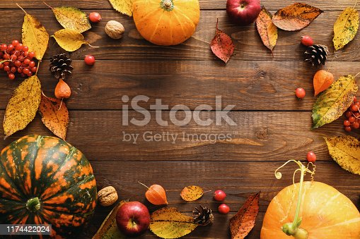istock Happy Thanksgiving concept. Autumn composition with ripe orange pumpkins, fallen leaves, dry flowers on rustic wooden table. Flat lay, top view, copy space. 1174422024