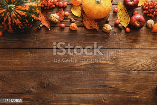 Happy Thanksgiving concept. Autumn composition with ripe orange pumpkins, fallen leaves, dry flowers on rustic wooden table. Flat lay, top view, copy space.