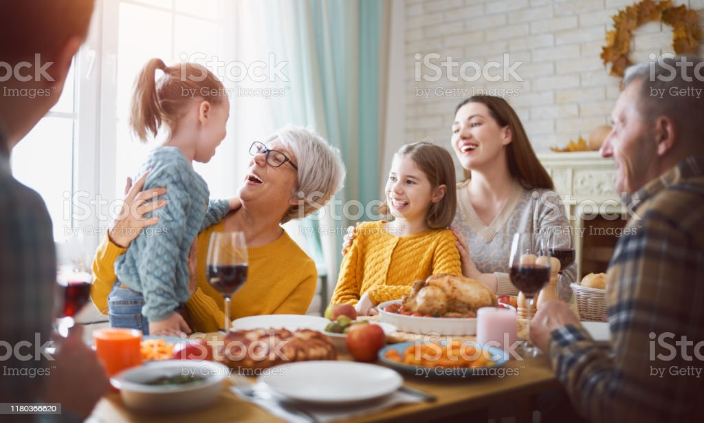 Happy Thanksgiving Day Happy Thanksgiving Day! Autumn feast. Family sitting at the table and celebrating holiday. Grandparents, mother, father and children. Traditional dinner. Adult Stock Photo