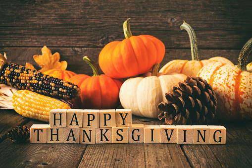 Happy Thanksgiving greeting on wooden blocks against a rustic wood background with pumpkins and autumn decor. Vintage style.