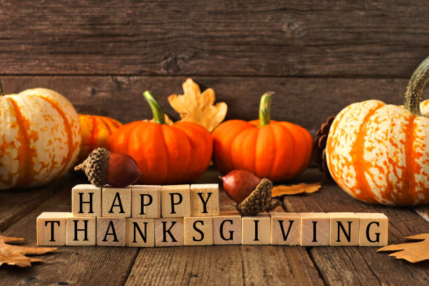 Happy Thanksgiving greeting against rustic wood with pumpkins and autumn leaves stock photo