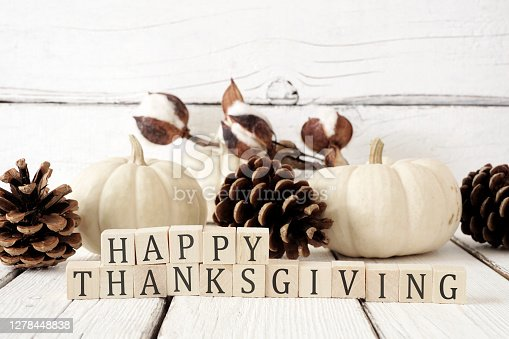 Happy Thanksgiving greeting on wooden blocks against a white wood background with white pumpkins and brown autumn decor