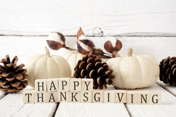 happy thanksgiving greeting against white wood with white pumpkins and brown autumn decor - autumn stock pictures, royalty-free photos & images