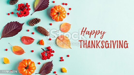 Happy Thanksgiving greeting card with leaves, pumpkins, rowan berries on mint background. Fall, autumn, thanksgiving concept.