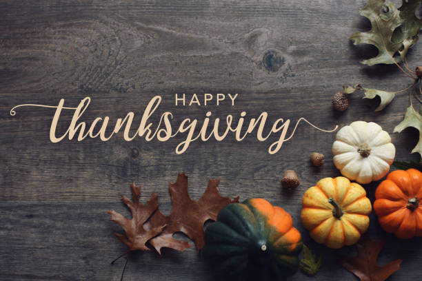 happy thanksgiving greeting text with fall pumpkins, squash and leaves over dark wood background - thanksgiving стоковые фото и изображения